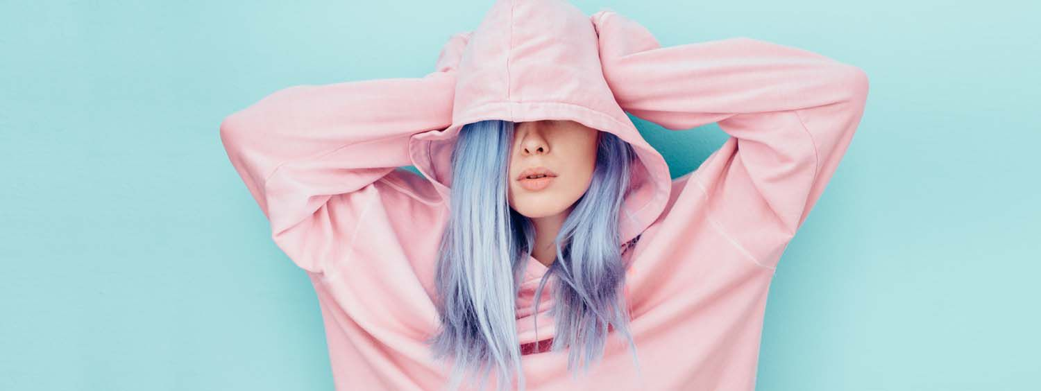 Woman with pastel violet-colored hair wearing a pink hoodie resting her hands on her head