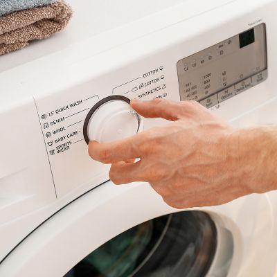 Hand von einem Mann, der gerade ein Waschprogramm an einer weißen Waschmaschine auswählt