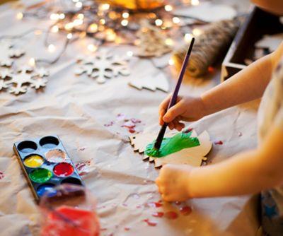 Adventskalender basteln, Kind bemalt einen Tannenbaum mit Tusche