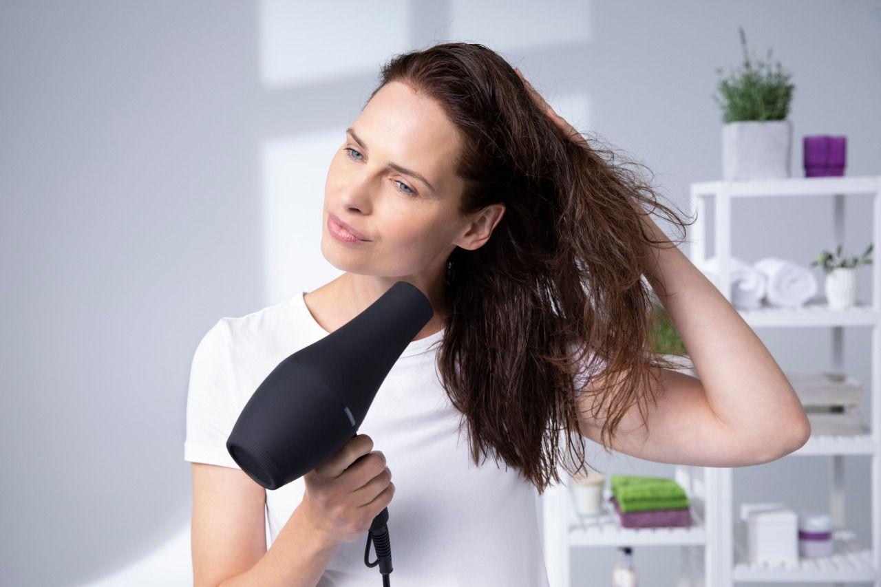 Chica con plancha de alisado pelo largo negro