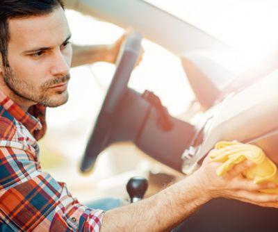 Autoinnenreinigung, Mann wischt die Armatur seines Autos