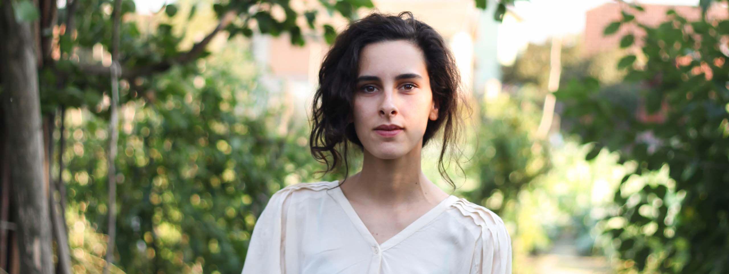 Jeune femme brune avec une coiffure romantique ondulée et une blouse blanche