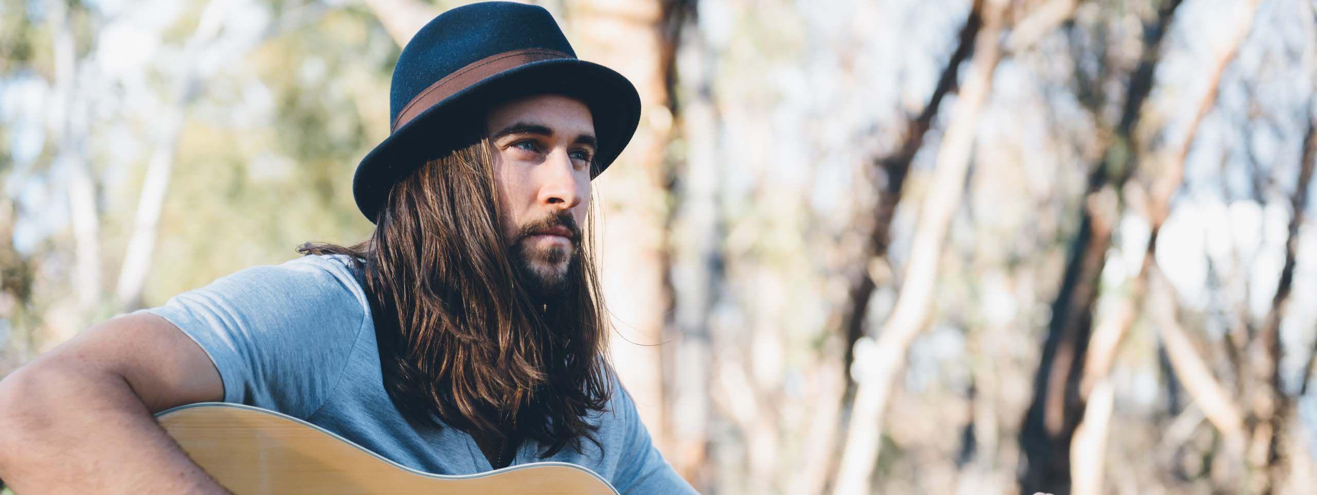 Moški z dolgimi lasmi in klobukom, ki igra na kitaro