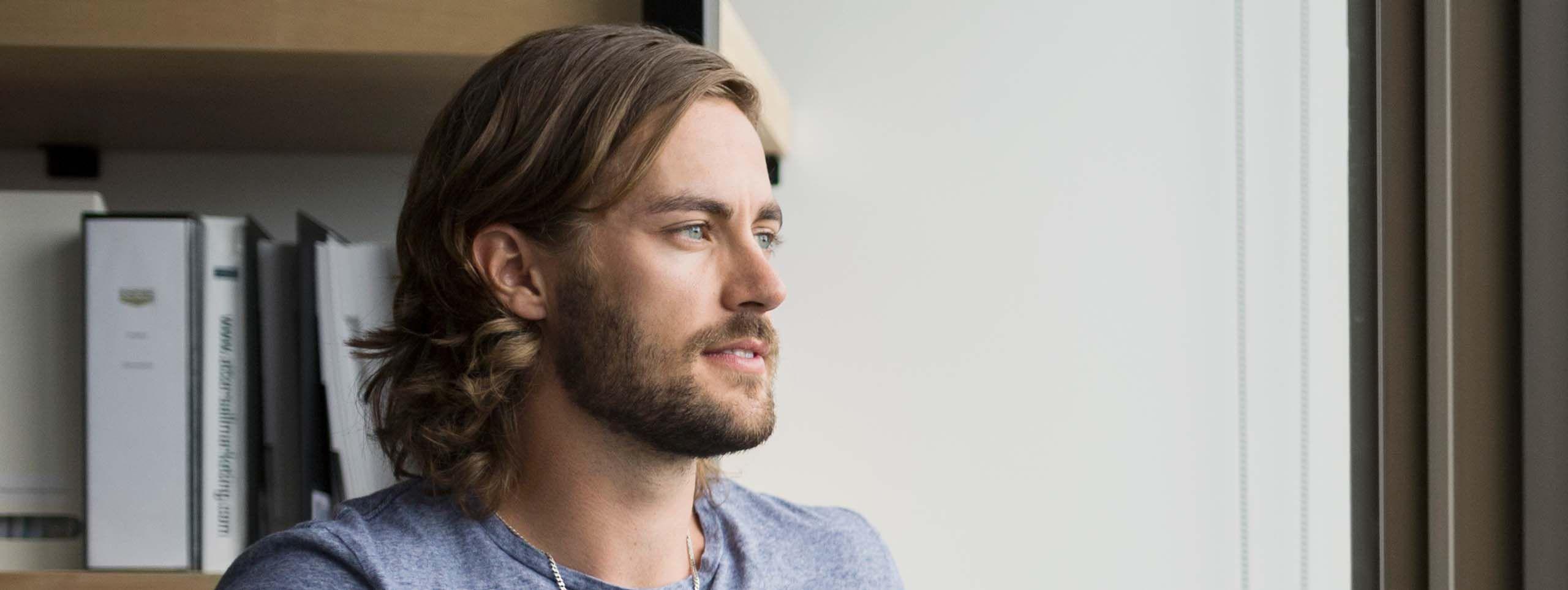Moški z daljšimi lasmi in brado, ki v roki drži skodelico in gleda skozi okno