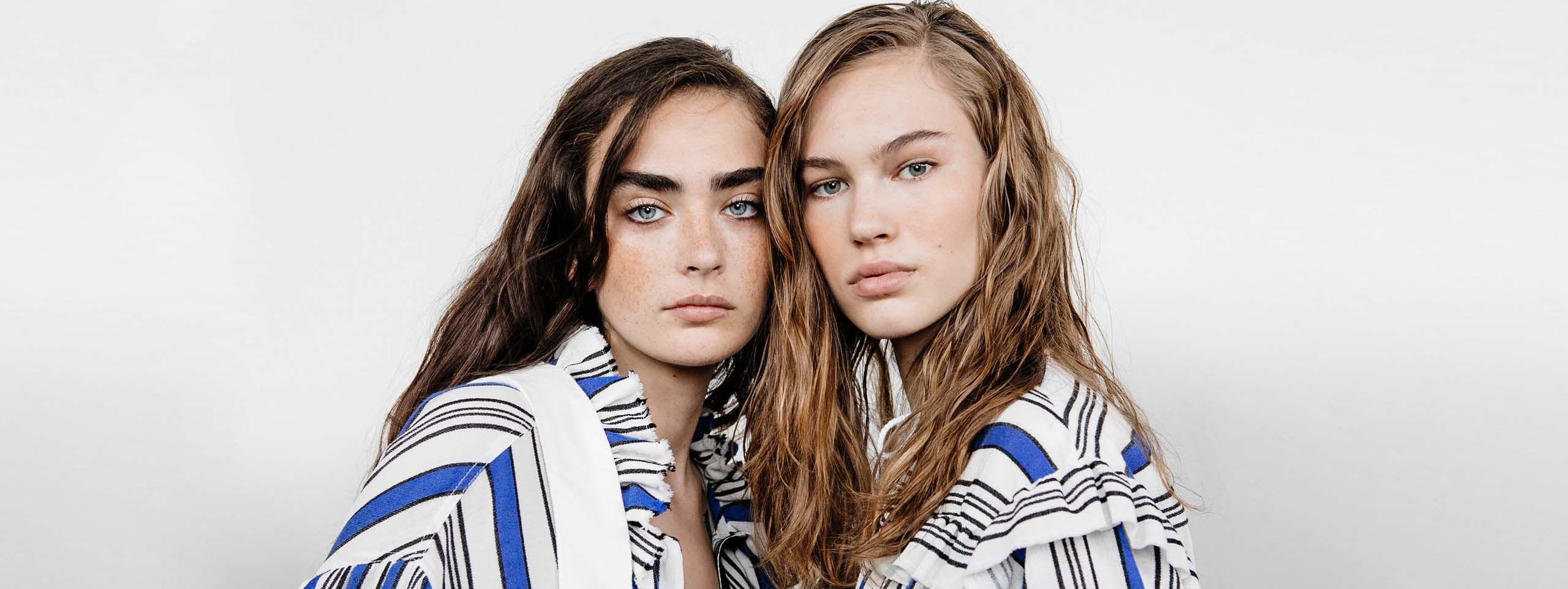 Dve žene - smeđokosa i plavuša - sa usklađenom garderobom, lepljivom, srednje dugom kosom i masnim skalpom.