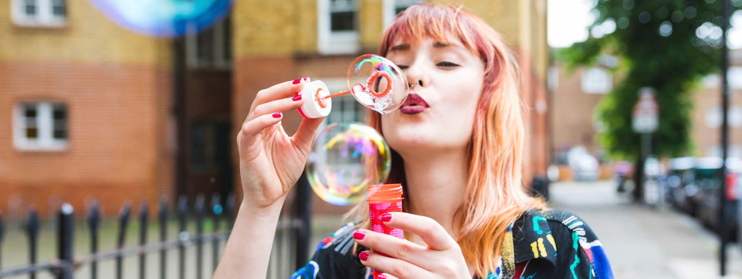 Mlada žena sa kosom jednoroga koja duva balone
