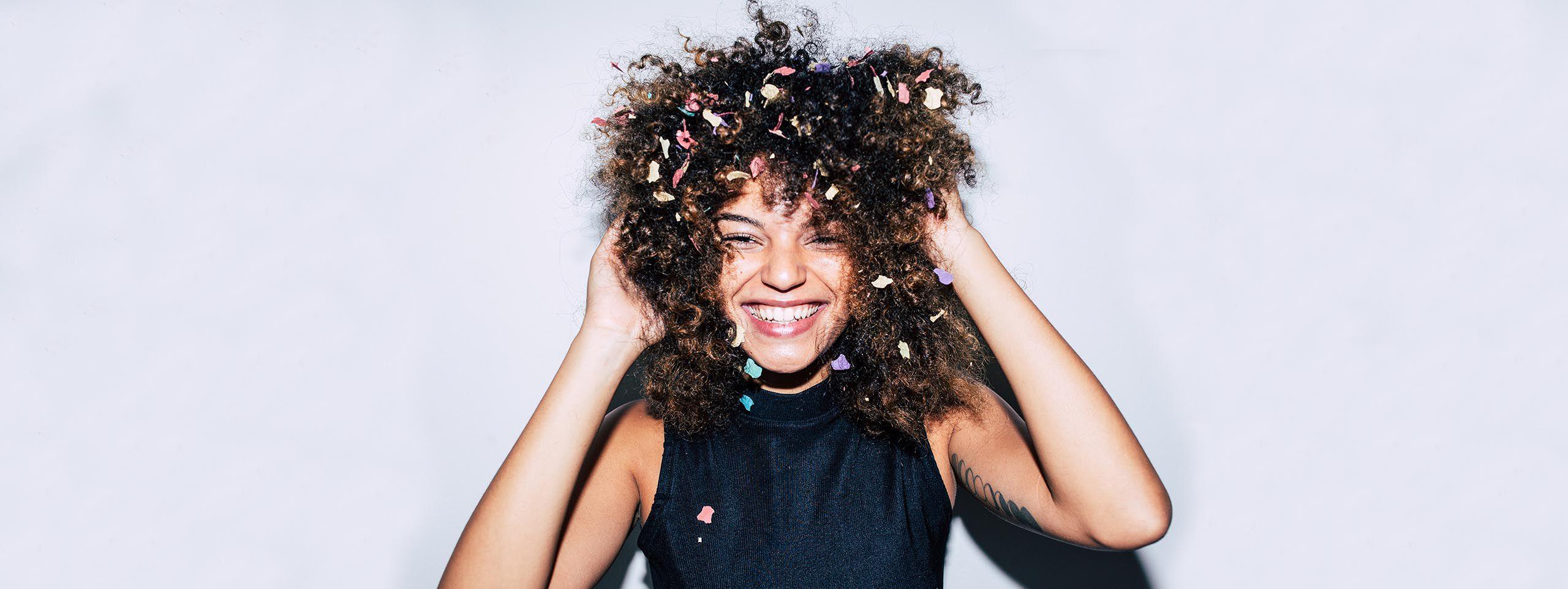 Žena s kovrčama i konfetima u kosi