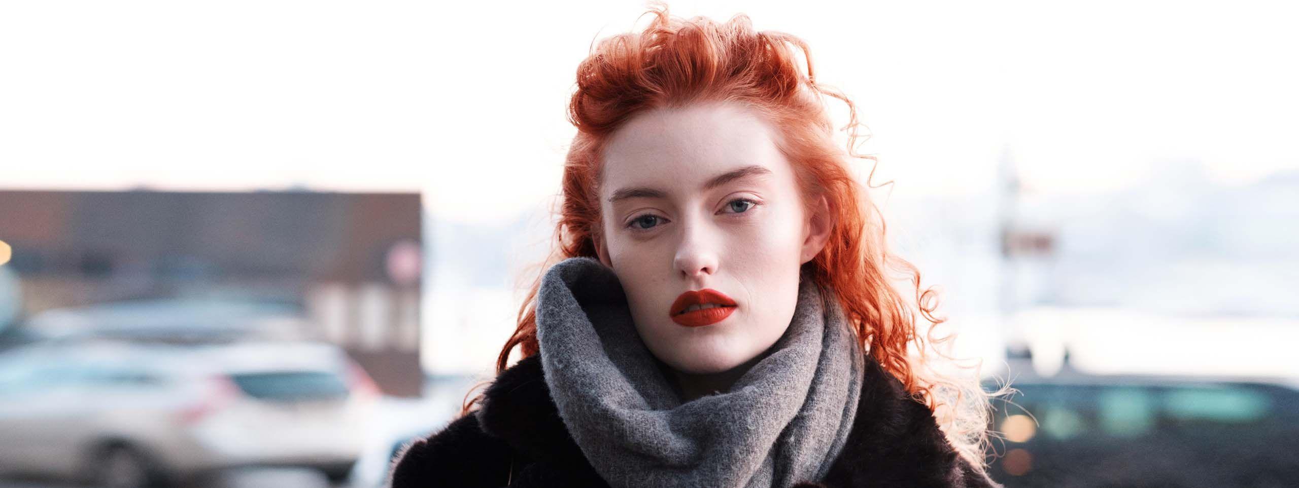 Mlada žena svetle puti sa zimskom jaknom, šalom i kovrdžavom kosom u boji Living Coral