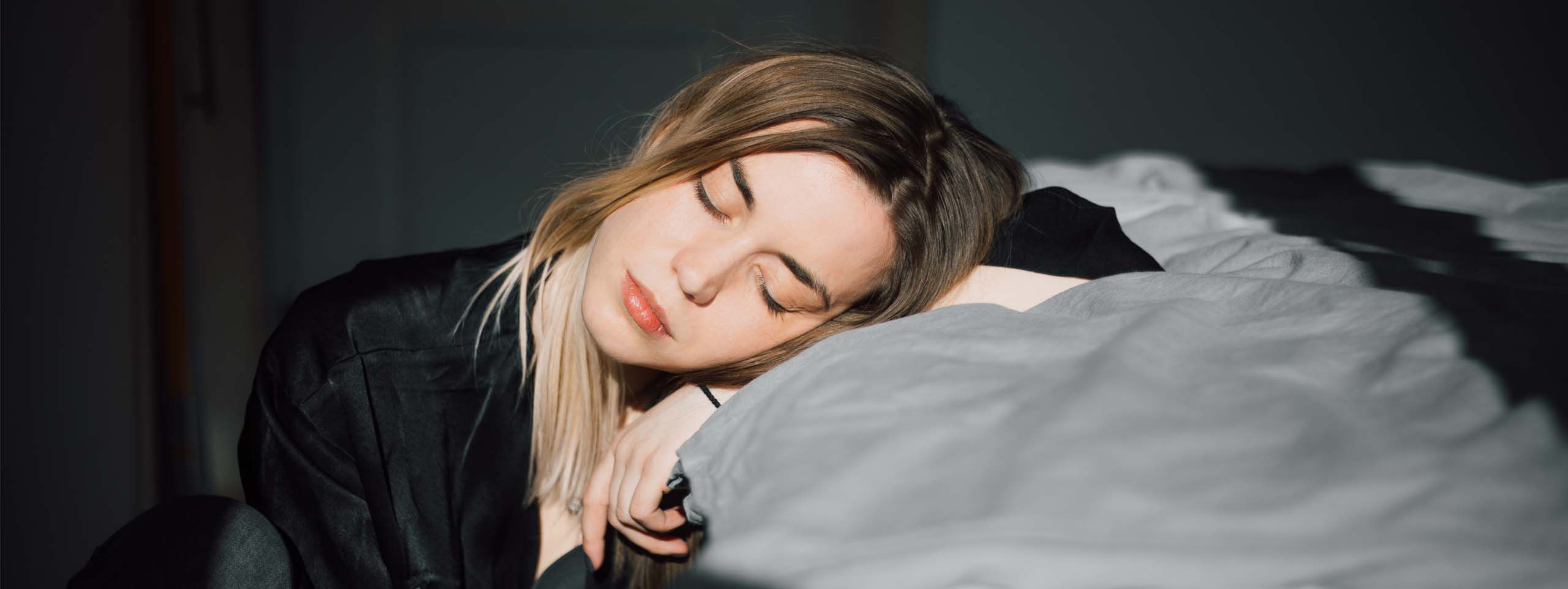 Young woman with zigzag part closing her eyes and resting her head on her arm