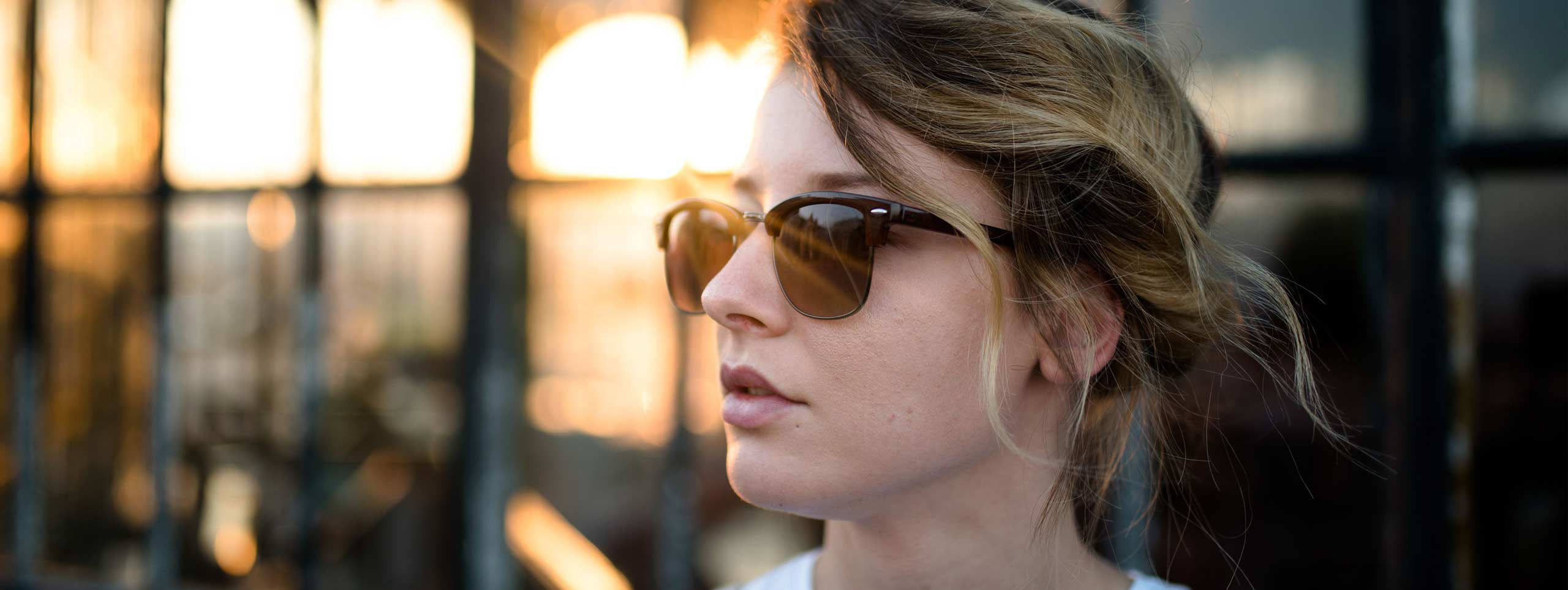Ženska s sončnimi očali, ki opazuje sončni zahod