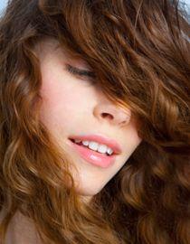 Kobieta z długimi bązowymi kręconymi włosami