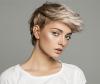Portrait einer jungen Frau mit einer blonden Kurzhaarfrisur auf grauem Hintergrund, die den Betrachter direkt anschaut