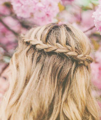 Gros plan sur une tresse cascade réalisée sur des cheveux blonds.
