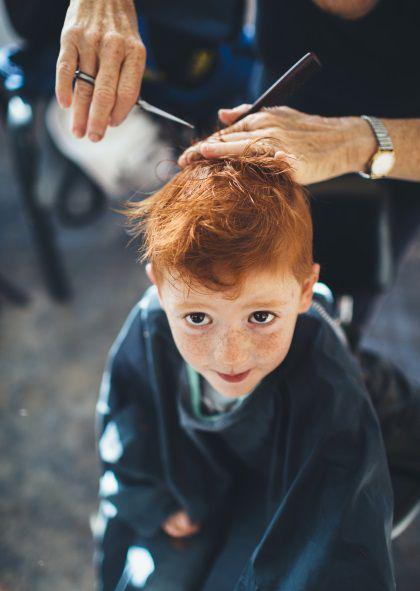 Garçon roux en train de se faire couper les cheveux par sa grand-mère.