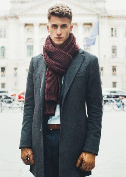 Homme élégant posant dans la rue avec une coupe en brosse moderne.