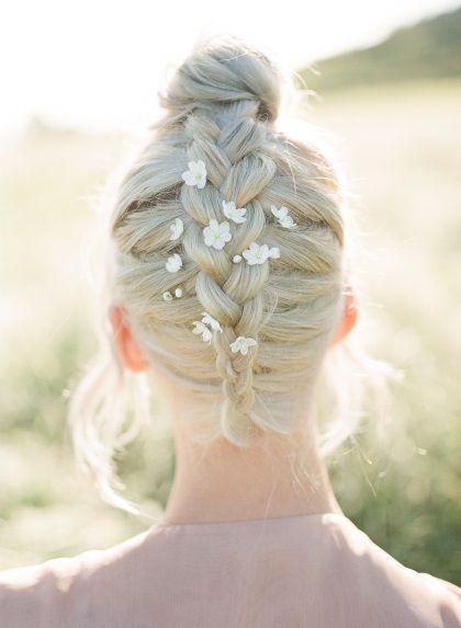 Femme blonde vue de dos avec une tresse hollandaise inversée et des fleurs dans les cheveux.
