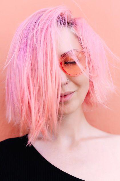 Femme aux cheveux rose bonbon avec un carré asymétrique ondulé et des lunettes roses.