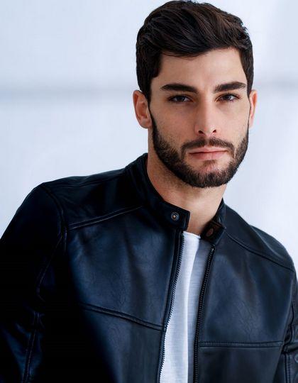 Homme avec une barbe et des cheveux bruns portant une raie de côté.