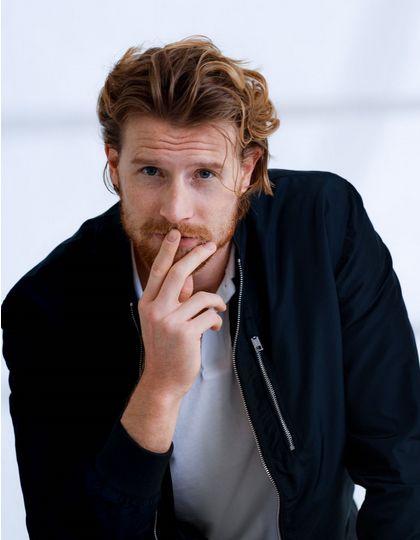 Homme avec une barbe et des cheveux roux coiffés-décoiffés.