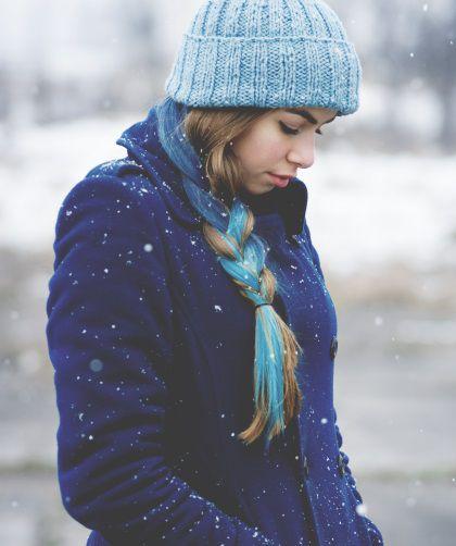 Femme de profil avec des cheveux blonds et des mèches bleues tressés et un bonnet bleu sous la neige.