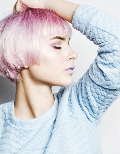 Femme avec une coupe au bol rose et un pull bleu ciel