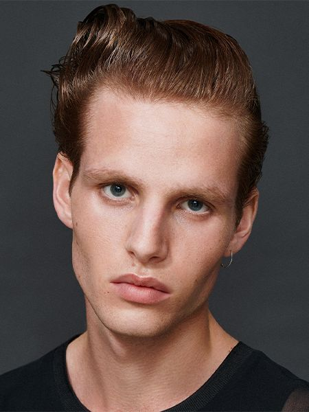 Man with gelled back hair, looking right at camera