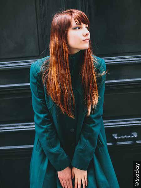 Jeune femme avec des cheveux teints en roux et un manteau bleu-vert