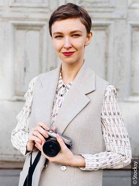 Portrait de femme brune avec une coupe pixie et un appareil photo entre les mains