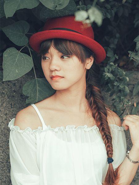 Femme avec un chapeau rouge rond, une frange rideau et une tresse poisson