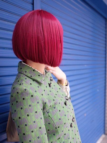 Femme vue de dos avec des cheveux rouge cerise et un carré plongeant.