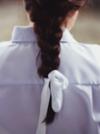 Rückansicht einer dunkelhaarigen Frau mit geflochtenem Haar und einer weißen Schleife