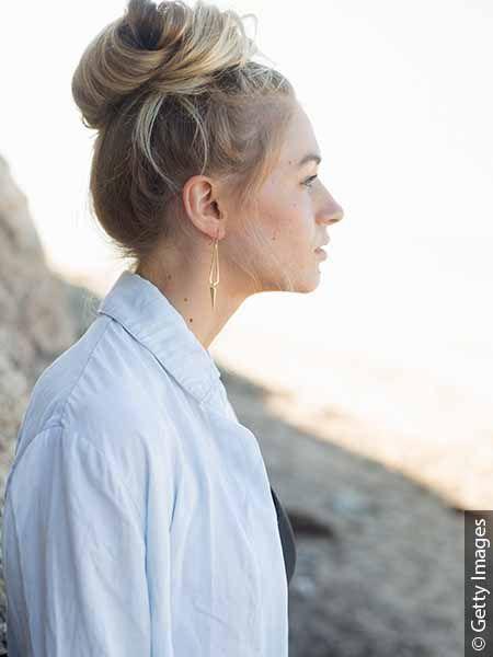 Profil de femme blonde avec un chignon haut et une chemise bleue