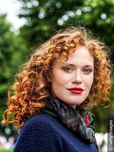 Donna con capelli rossi ricci fino alle spalle