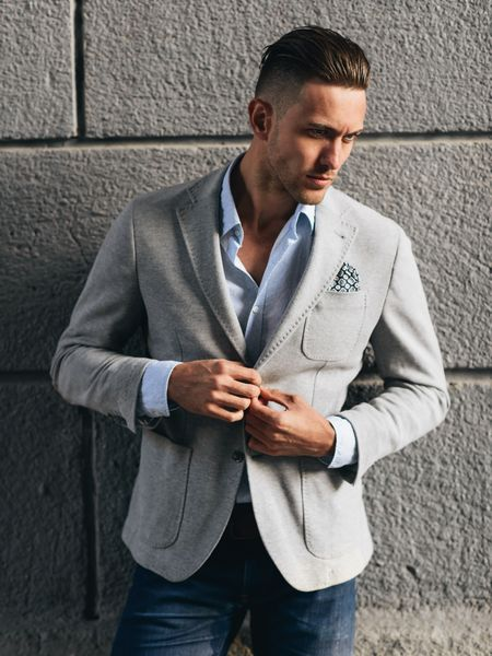 Man with fade haircut, wearing a suit jacket and jeans