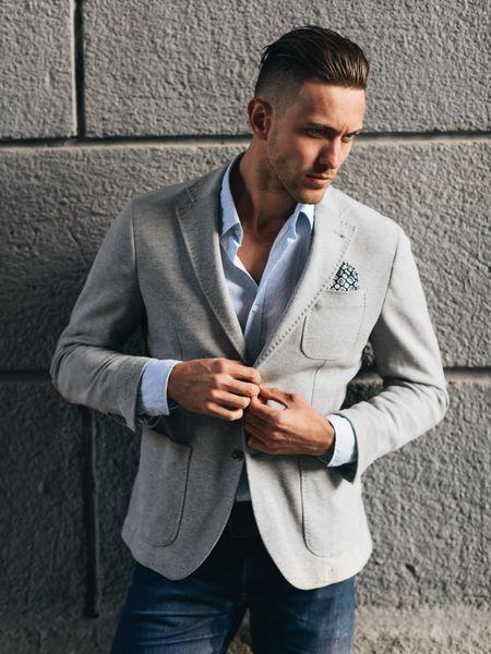 Muškarac s fade frizurom u sakou i trapericama
