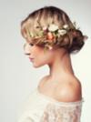 Seitenprofil einer blonden Frau, die ihren Bauernzopf als ganzen Haarkranz mit Blüten verziert trägt