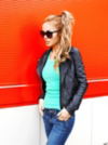 Woman with a ponytail and sunglasses standing in front of a red and white wall