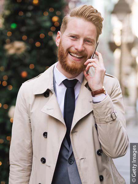 Uomo con capelli rossi tirati indietro con gel e barba che sorride al telefono