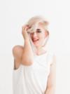 Platinblonde Frau mit weißem Top fässt sich in die Haare