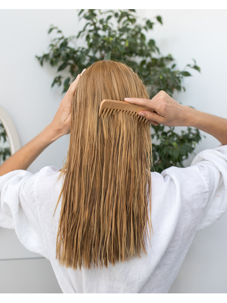 Žena češlja dugu plavu kosu