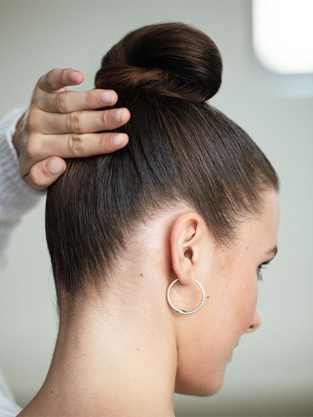 Woman with brown hair wearing a bun.