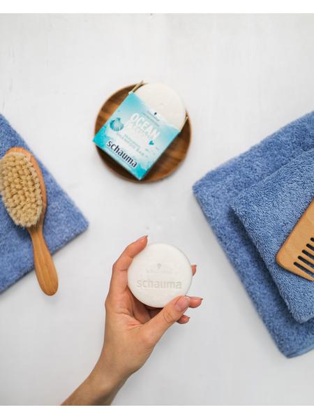 A hand holding a Schauma shampoo bar
