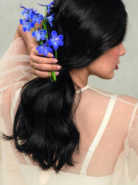 Donna con lunga coda di cavallo nera, vestita di bianco, con accessori floreali per capelli azzurri.