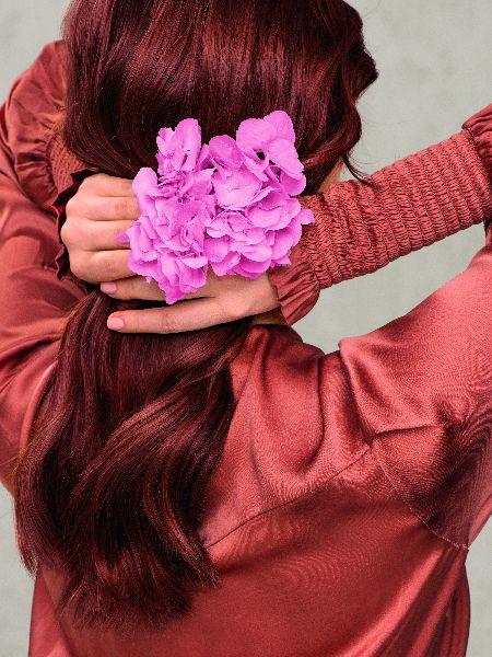 Frau mit leuchtend roten Haaren hält sich eine pinke Blume ins Haar.