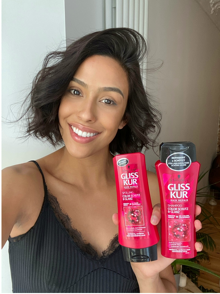 Woman with healthy curls holding Gliss Color Protect products