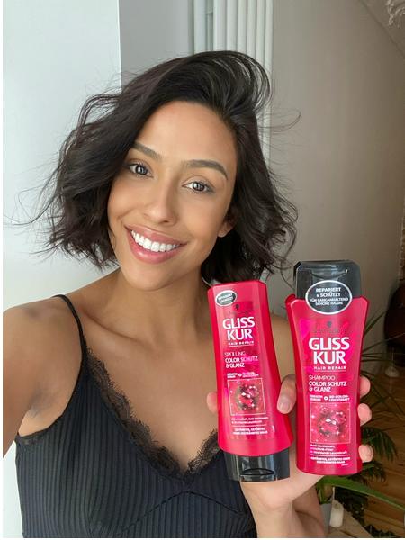 Žena sa zdravom kovrčavom kosom drži Gliss proizvode