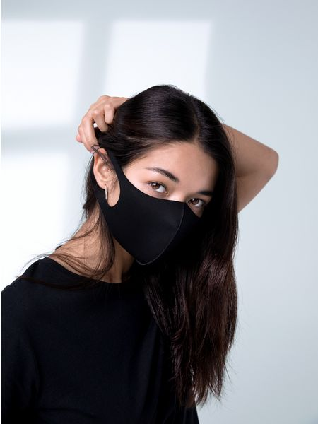 Woman with black hair with hair caught in mask