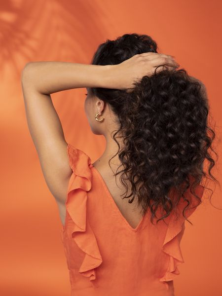 Woman with black curly hair, pulling it into a ponytail