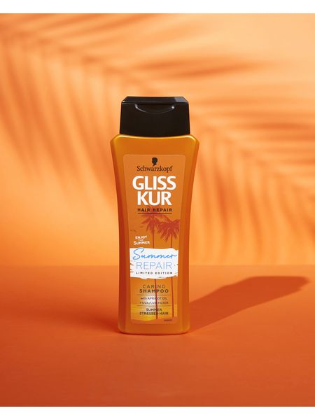 Bottle of Gliss Summer Repair Shampoo with orange background