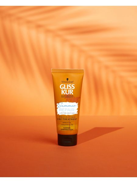Bottle of Gliss Summer Repair Protecting 2 in 1 Treatment with orange background